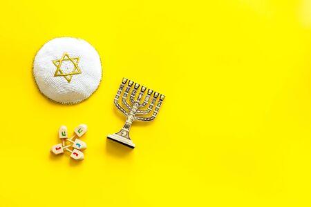 Jewish Kippah Yarmulkes hats with menorah on yellow table. Top view, copy space