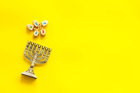 Menorah - traditional Jewish Candelabra - holiday Hanukkah concept on yellow background, top view, copy space