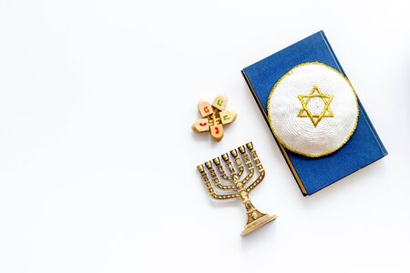 Jewish Kippah Yarmulkes hats with Star of David on Prayer book with menorah. Religion Judaisim symbols on white table top view copy space