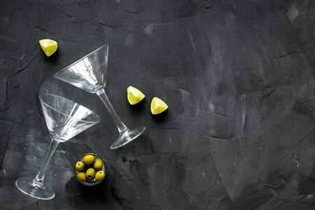 Aperitif drink concept. Martini glasses near olives and lemon on grey background.