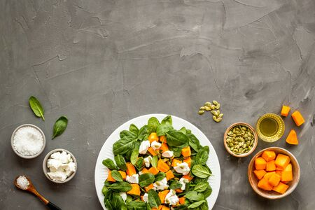 Cooking salad with pumpkin and basil. Ingredients on grey background top-down.