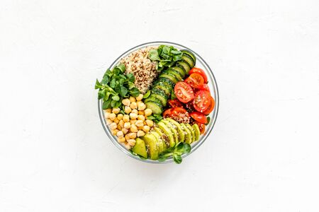 Healthy salad bowl with quinoa, avocado and chickpeas on white background top-down.
