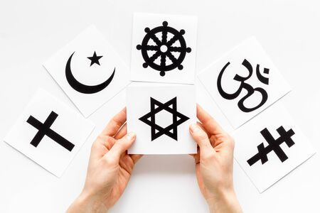 Choose religion concept. Hands with Jewish star of David near world religions symbols on white background top view Stock Photo