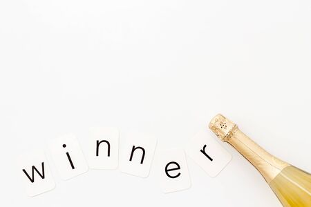 Winner is concept. Announcement design mockup with champagne on white background top view.