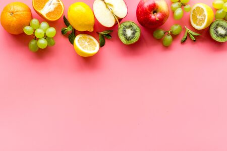 Fresh fruits background with citruses, apple, kiwi and grape on pink table top-down.