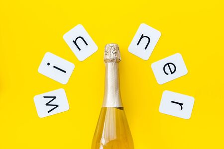Winner congratulation concept with champagne on yellow background top view