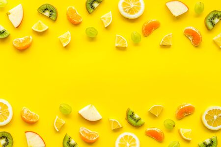 Slices fruites frame. Fruit salad concept with citruses, aplle and kiwi on yellow background top-down.