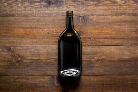 Wine bottle on wooden background top view. Imagens