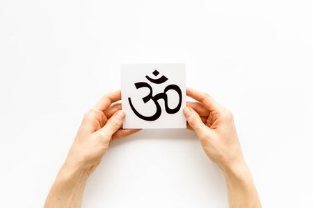 Om - Buddhist inner peace symbol - in hands on white desk top view