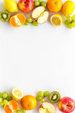 Oranges, lemon, apple, kiwi and grape - healthy food concept with fruits - on white background top-down frame copy space