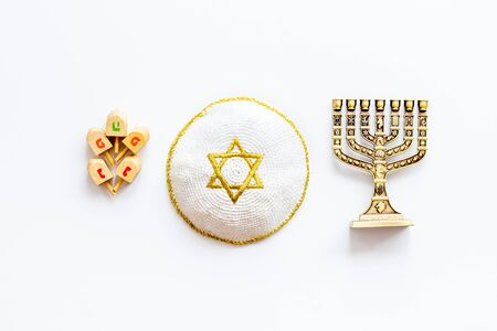 Jewish Kippah Yarmulkes hats with menorah on white table. Top view