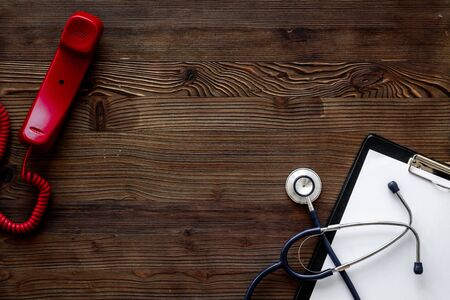 Doctor on phone. Handset near stethoscope on wooden desk top view copy space 免版税图像