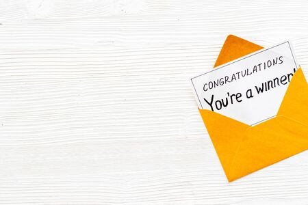 Youre a winner. Envelope with congratulation card on white wooden table top view copy space