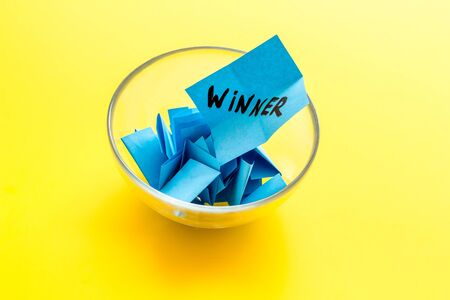 Winner selection. Paper pieces for lottery in vase on yellow table