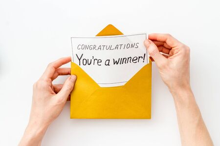 Congratulations Youre a winner. Hands holding envelope with letter. White background top view Imagens