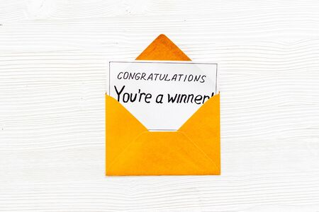 You're a winner. Envelope with congratulation card on white wooden table top view.