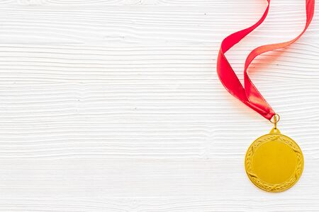 Gold medal with red ribbon - winner, success concept - on white wooden background top view copy space
