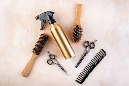 Hairdresser set in beauty salon. Combs, scissors, spray on beige desk top-down