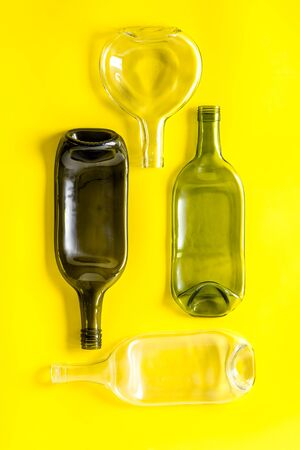 Pattern of bottles on yellow background top view.
