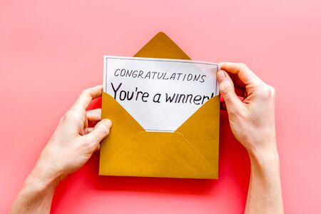 Congratulations Youre a winner. Hands holding envelope with letter. Pink background top view