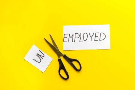 Unemployed - employed - torn paper sheet, sciccors on yellow background top view. Hiring concept.