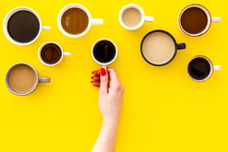 Coffee addiction. Mug in hand, many cups on yellow background top view copy space