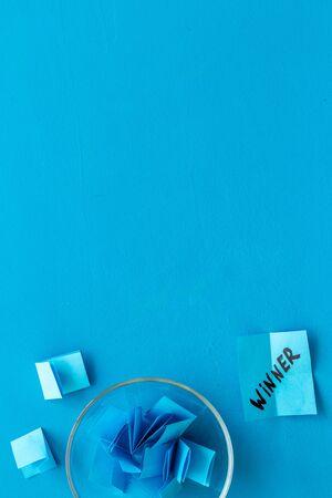 Paper pieces - random winner selection - blue desk top-down copy space