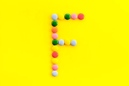 Letter F - alphabet made with sweets on yellow background from above.