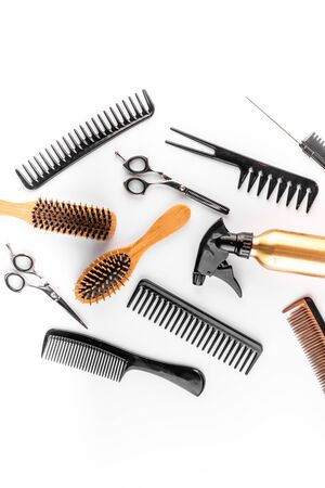 Hairdressing instruments. Combs, scissors and spray on white desk from above. Archivio Fotografico