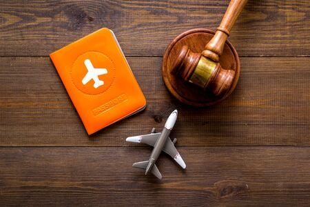 Flight cancellation. Airplane, passport, judge gavel on wooden desk top-down