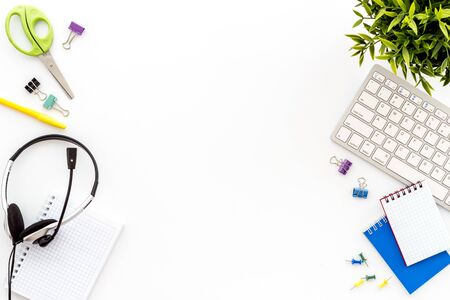 E-learning. Stationery, headphones and keyboard on white table top-down frame copy space