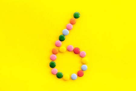 Candies font. Number 6 - six - on yellow background top view