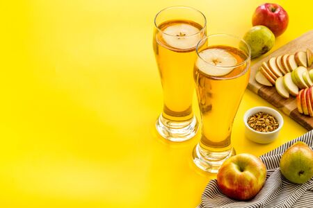 Glasses of beer with apple and peer on yellow table copy space Banque d'images