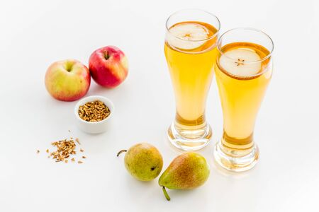Glasses of beer with apple and peer on white desk
