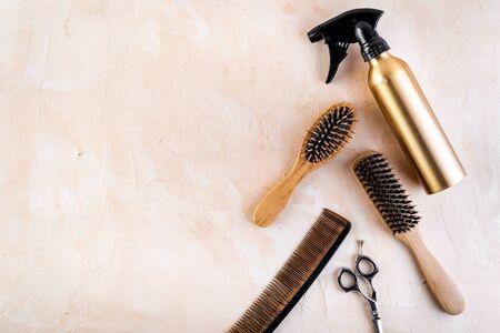 Hairdresser set in beauty salon. Combs, scissors, spray on beige desk top-down copy space Zdjęcie Seryjne