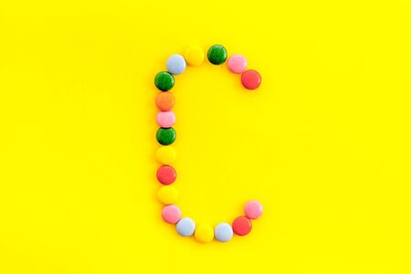 Letter C - alphabet made with sweets on yellow from above