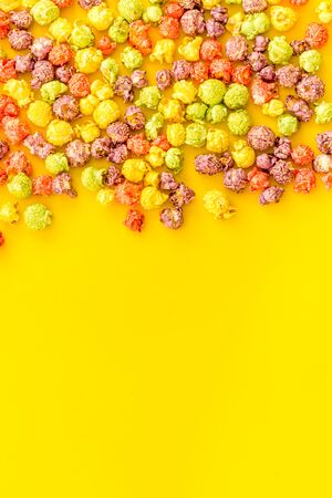 Flavored popcorn on yellow background top view space for text