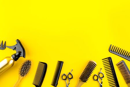 Hairdressing instruments. Combs, scissors on yellow table top view frame copy space Zdjęcie Seryjne