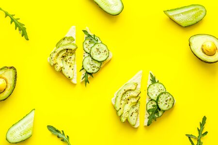 set of avocado sandwiches on yellow background top-down pattern