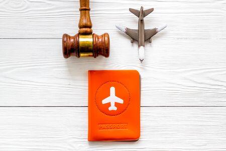 Flight cancellation. Airplane, passport, judge gavel on white wooden desk top-down