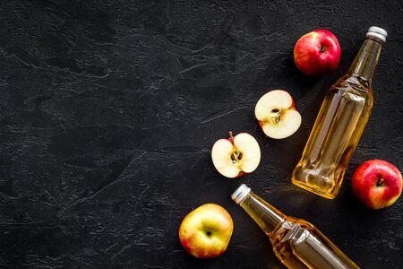 Apple cider vinegar bottle on black background top view copy space