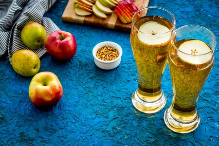 Glasses of beer with apple and peer on blue desk