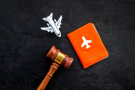 Flight cancellation. Airplane, passport, judge gavel on black desk top-down