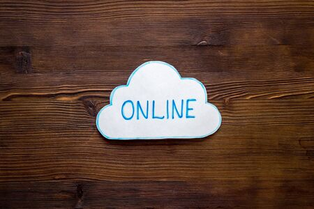 Cloud online networking concept. Paper bubble on wooden workplace
