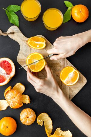 Hands making orange juice on curring board Standard-Bild