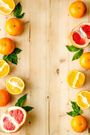 Frame of citrus - oranges and frapefruit - on wooden kitchen table. Copy space.
