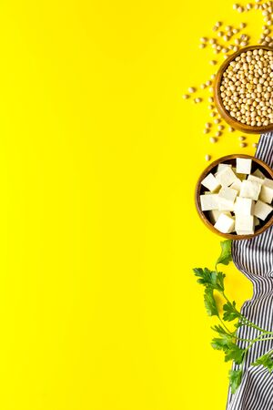 Tofu cubes in bowl and soybeans on yellow background top-down space for text