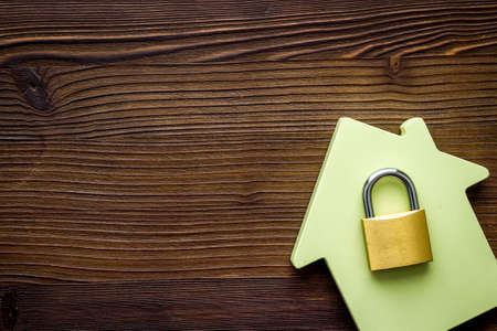Security concept - lock and house figure - on wooden desk top-down space of text