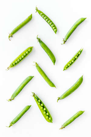 Pattern of fresh green pea pod with beans on kitchen desk. Top view