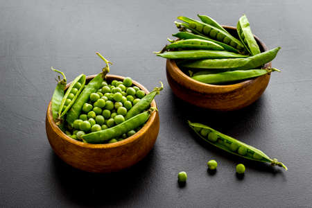 Bowl of green pea pod with beans on kitchen desk. Close up